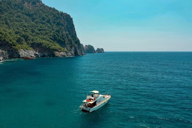 Парусник в море в вечернем солнечном свете над красивыми большими горами, роскошное летнее приключение, активный отдых в средиземном море, турция