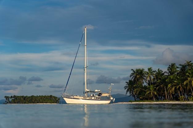 Парусник в море на фоне красивых островов и пальм. приключение, концепция активного отдыха.