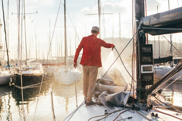 ヨットの所有者またはヨットマンは、日没時にマリーナにドッキングまたは駐車したときに、ホースを使用してヨットデッキから塩水を洗い流します