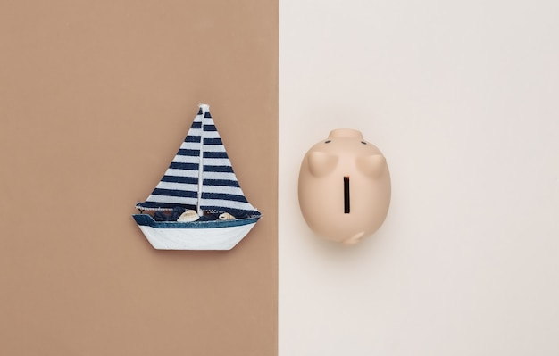 Sailboat and piggy bank on brown beige background. travel concept. top view