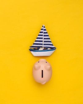 Sailboat and piggy bank on yellow background. travel concept. top view
