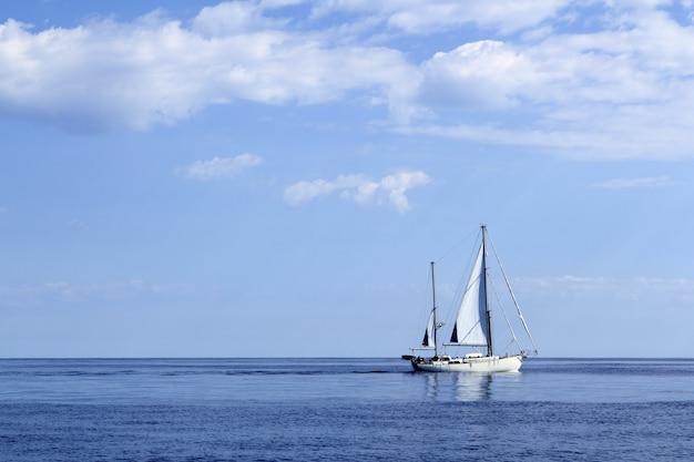 青い海の地平線の海でセーリングヨット