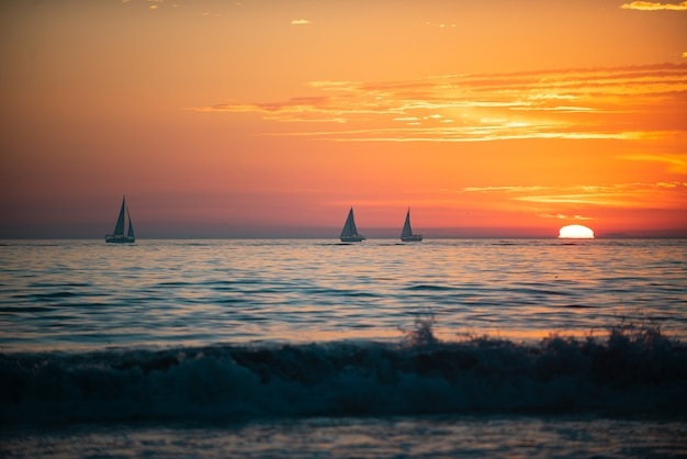 Sailboat at sea panoramic view of sunset over ocean beautiful serene scene sea sky concept sunrise c...