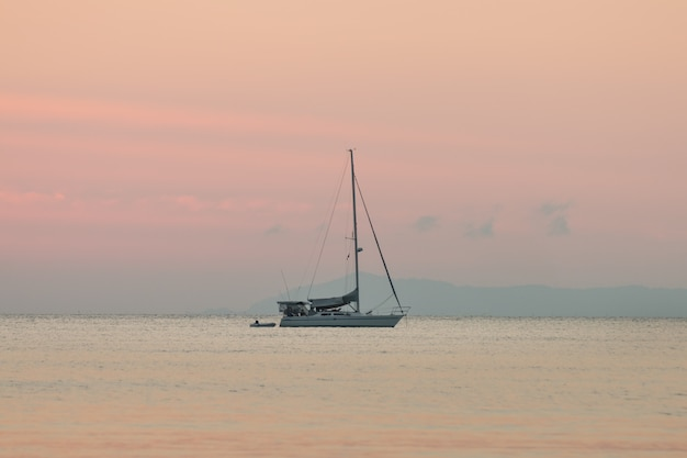 Sailboat in the sea of summer background and sunset in the evening time.