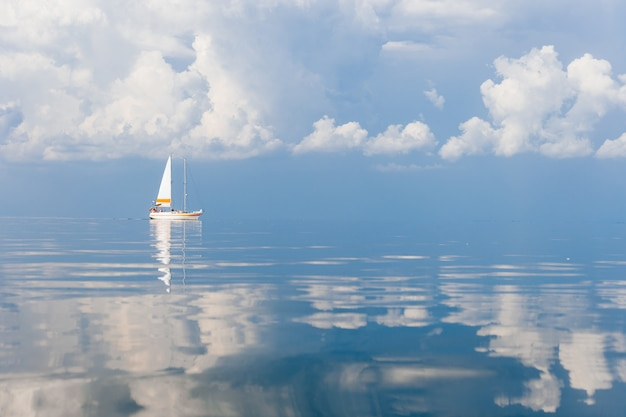 Sailboat in sea in sunny day on fabulous fairy tale picturesque seascape with clouds reflected in water.