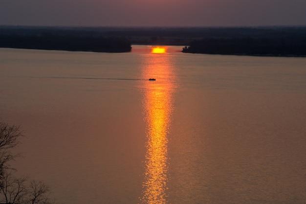 Фантазия о закате на парусной лодке с силуэтом лодки, плывущей по своему пути на фоне яркого красочного заката с птицами, летящими в строю на фоне неба, наполненного оранжевым и желтым цветом.