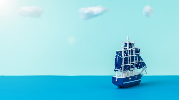 A sailboat with blue sails sailing away from the shore. the concept of travel and adventure. installation.