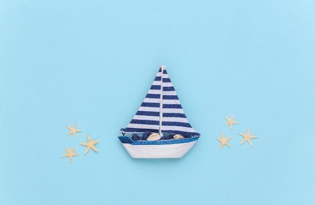 青い背景にヒトデとヨット。旅行のミニマリズムの概念。上面図。フラットレイ