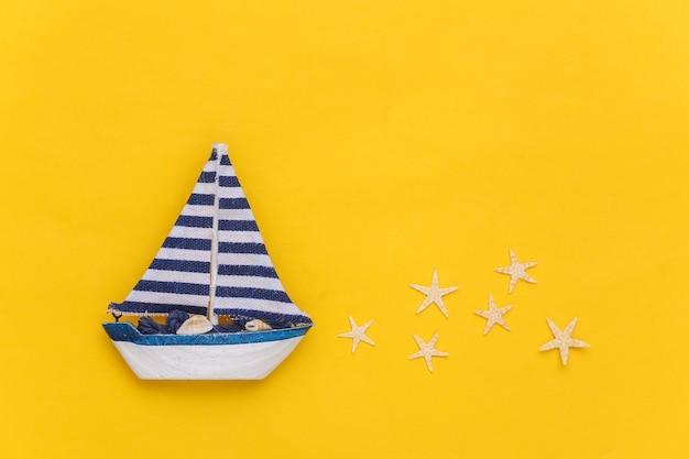 黄色の背景にヒトデとヨット。旅行のミニマリズムの概念。上面図。フラットレイ