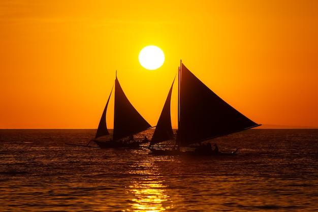 熱帯の海に沈む夕日のヨット。シルエット写真。