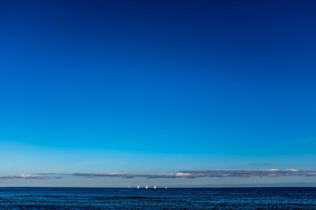 Парусные лодки на линии горизонта на море, глядя на вид с пляжа барселоны