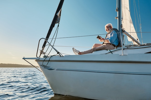 Sailing alone side view of a relaxed senior man sitting on the side of sailboat or yacht deck