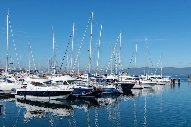 Парусные и моторные яхты в морском порту в яркую солнечную погоду на фоне голубого безоблачного неба