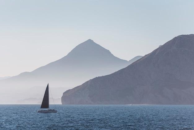 Парусная лодка в море на фоне красивых больших гор, шикарное летнее приключение, активный отдых на средиземном море.