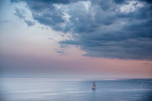 아름다운 분홍색 일몰 하늘에서 잔잔한 바다에 범선