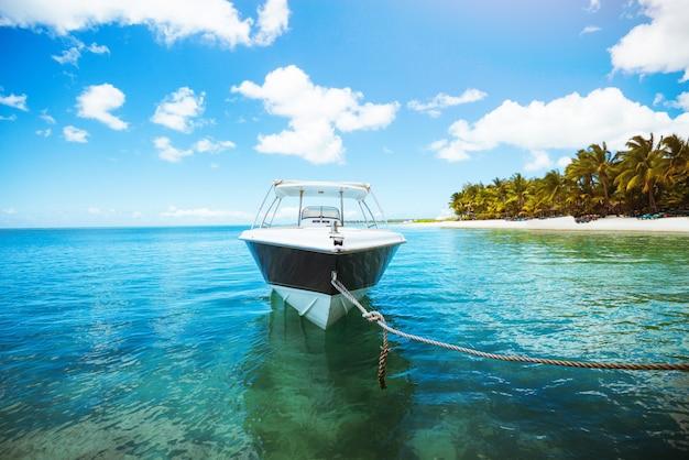 Парусная лодка на кристально голубой воде океана. тропическая сцена