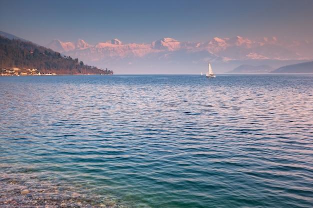 Парусная лодка на озере тун, бернский оберланд, швейцария