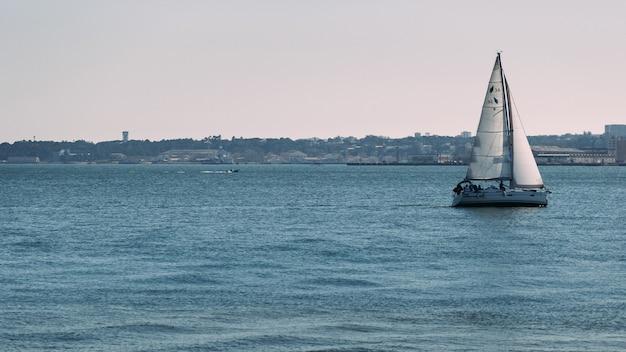 Sailing boat on the sea with urban coast
