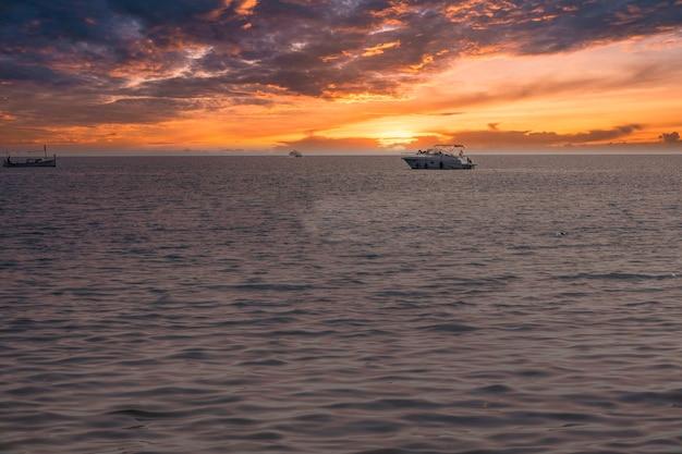 Парусные лодки в море на драматическом закате