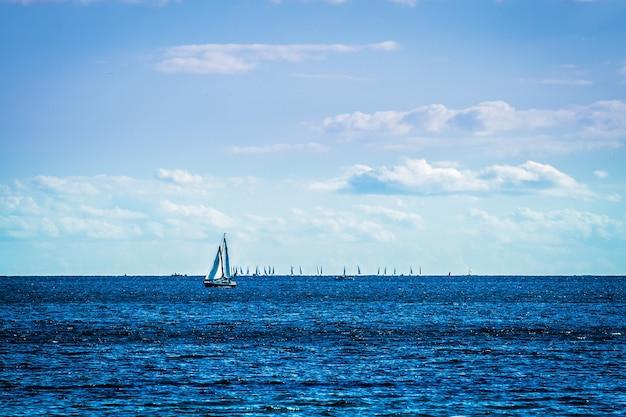 Парусные лодки на море с голубым небом