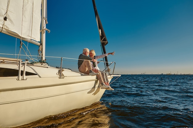 に浮かぶ帆船やヨットのデッキの横に座って幸せな引退した家族のカップルをセーリング