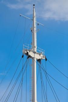 Парусная мачта корабля на фоне голубого облачного неба