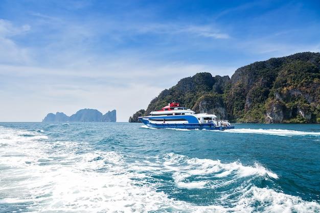 열대 섬을 배경으로 바다에서 항해 후면 보기 모터 트랙과 물 위의 파도
