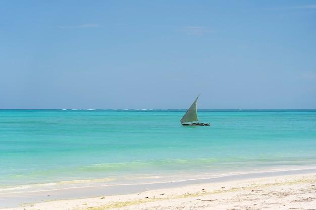 Парусник и голубое небо над волнами морской воды на острове занзибар, танзания, восточная африка. концепция путешествия и природы