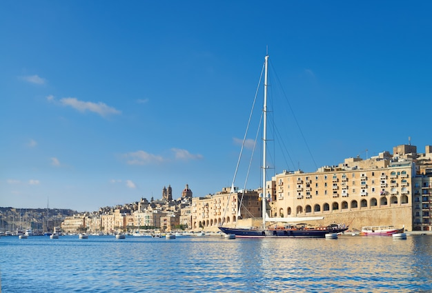 Sailing ship enters grand valetta bay on a bright day
