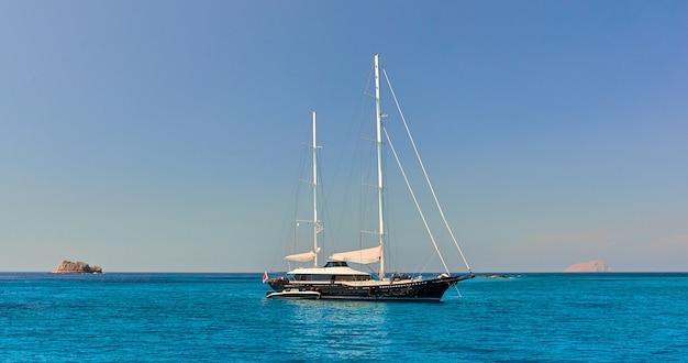 セーリング。外洋で白い帆を備えたヨットを出荷します。豪華なボート。旅行とアクティブなライフスタイルのコンセプト。