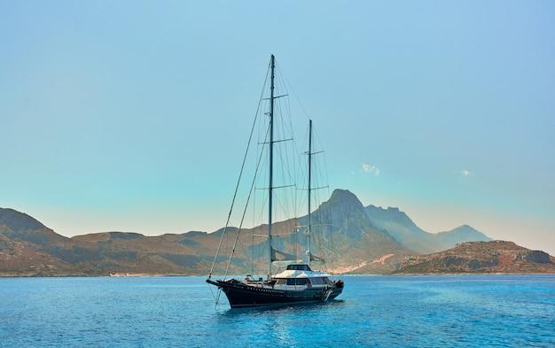 セーリング。山を背景に外洋で白い帆のヨットを出荷します。豪華なボート。旅行とアクティブなライフスタイルのコンセプト。