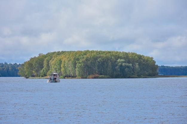 Переход к острову на озере на лодке, остров на озере, осеннее озеро