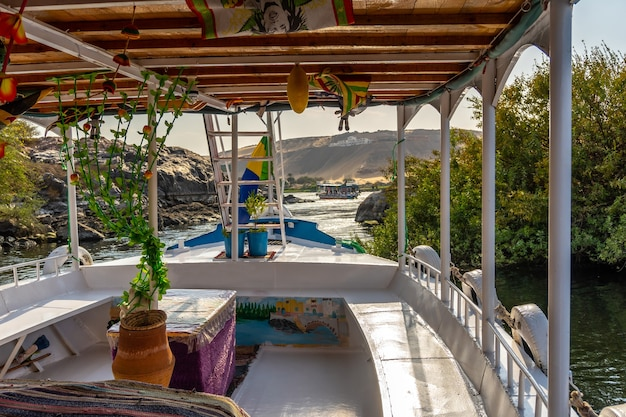 Sailing in a traditional egyptian boat on the nile river towards the nubian villages near the city of aswan. egypt