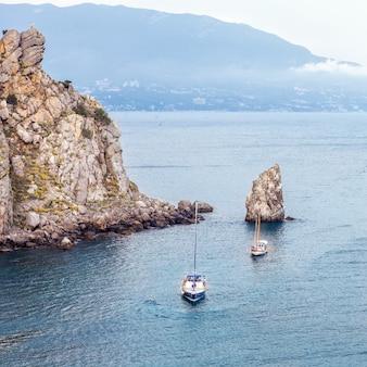 Парусная яхта и катер плывут по скалистому берегу черного моря среди обрывов и гор. природный ландшафт и морской пейзаж крым, россия.