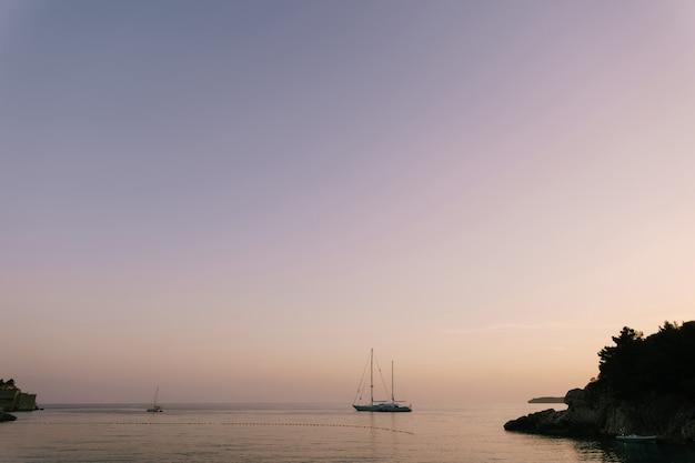 紫色の夕焼け空を背景に、海でセーリングヨット。