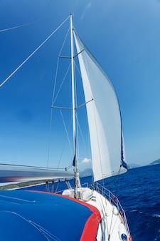 Парусная яхта на воде океана на восходе солнца с вспышкой и образом жизни на открытом воздухе