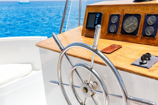 Sailing yacht control wheel and navigation implement.