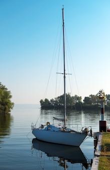 Парусная яхта в бухте. причал и яхты