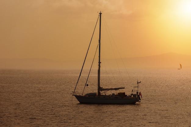 Парусная яхта заката, тонированная в теплые тона