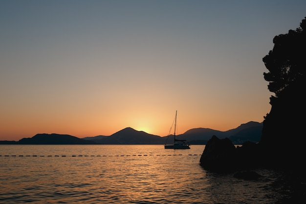 Sailing yacht sails out from behind the rocks at sunset