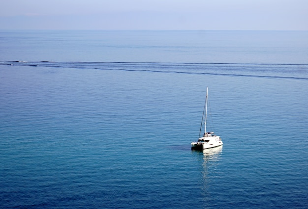 Sailing yacht on a tranquil ocean in tropea