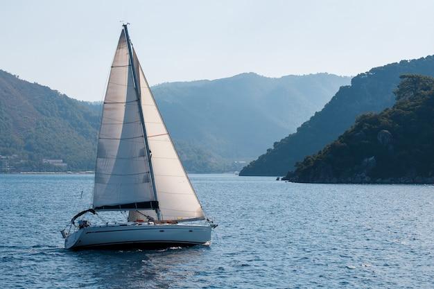 Парусная яхта с белыми парусами на волнистой морской бухте на фоне гор