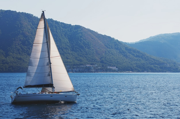 Sailing yacht with white sails on a wavy sea bay on a background of mountains