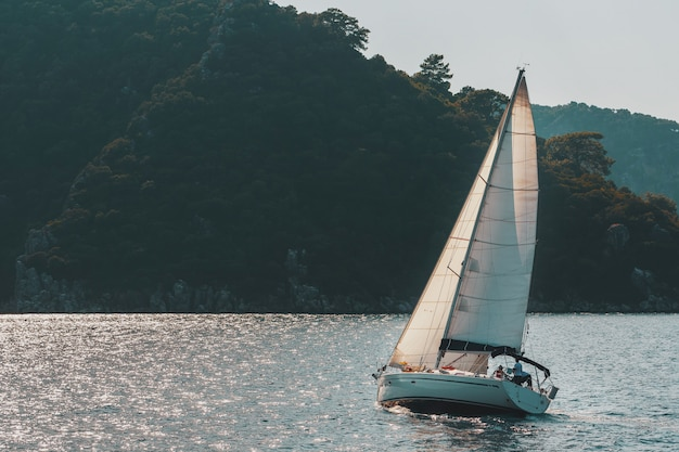 Sailing yacht with white sails on a wavy sea bay on mountains.