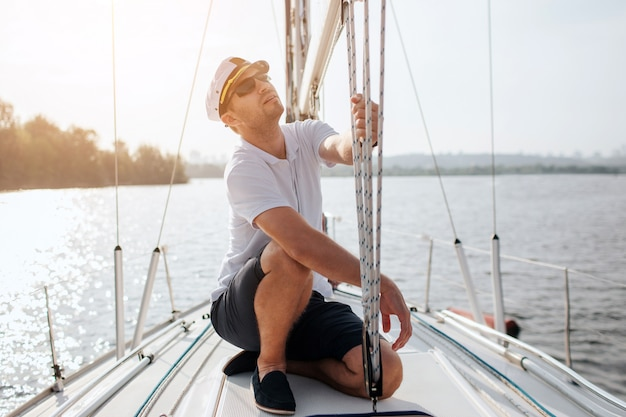 Sailor sits on board of yacht and look up. he holds ropes in hands. guy is concentrated. it is beautiful and sunny day outside.