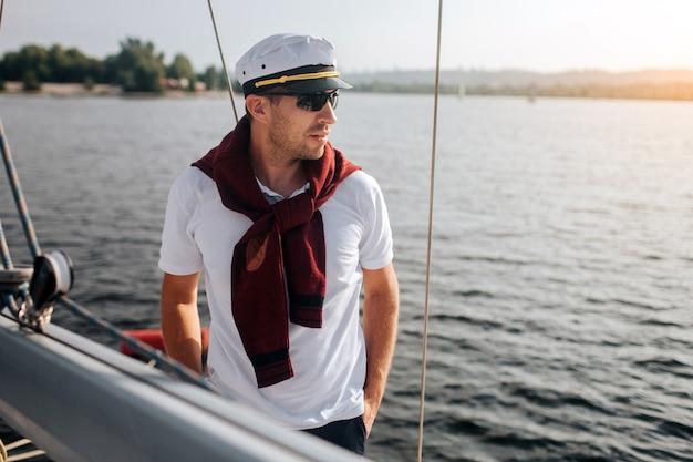 Матрос стоит на своей яхте. он держит руки в карманах и смотрит налево. мужчина хорошо сложен и стильный. он готов к поездке