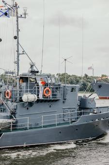 Матрос на борту военного корабля. русские военные корабли в реке волга в астрахани летом в пасмурный день. российские военные корабли.