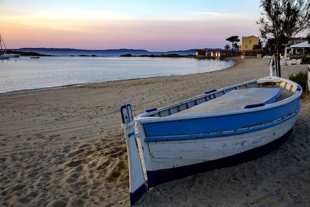 Пляж сен-клер с лодкой и зданиями на ней в окружении моря и холмов во франции