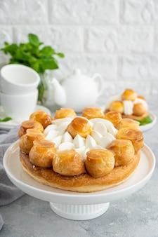 회색 콘크리트 배경에 흰색 접시에 프로피롤, 카라멜, 커스터드, 휘핑 크림을 넣은 생 오노레 케이크. 프랑스 전통 디저트. 공간을 복사합니다.