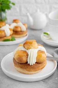 Торт saint honore с профитролом, карамелью, заварным кремом и взбитыми сливками на белой тарелке на сером бетонном фоне. традиционный французский десерт. скопируйте пространство.
